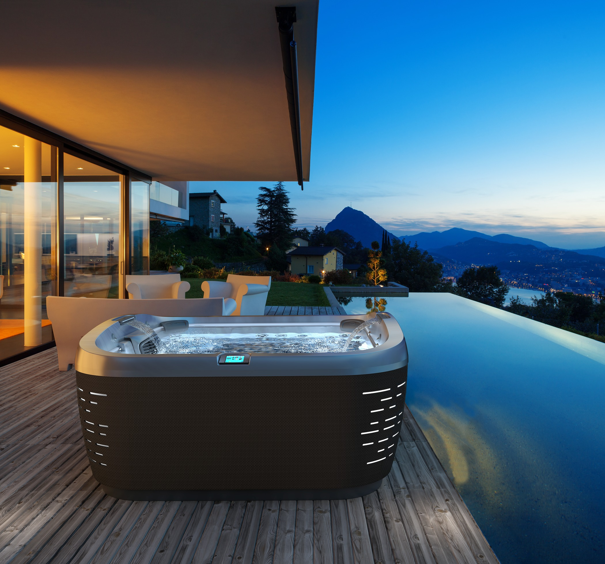 J-585 hot tub next to infinity pool at night