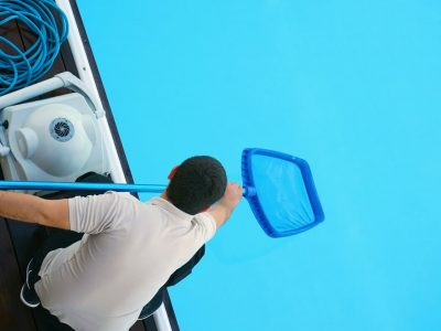 Service Technician cleaning a swimming pool